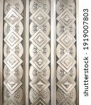 Small photo of Vertical rows of repeating circle shapes, flower petals, and diamond-oriented squares decorate an exterior wall. The architectural style appears to be art deco, perhaps by casting or relief.