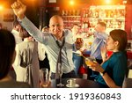 Small photo of Portrait of cheerful tipsy businessman drinking alcohol and having fun at corporate party in nightclub