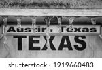 "Winter storm in Texas. Sign ""Austin, Texas"" behind icicles. Selective focus on icicles, black and white image."