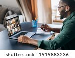 Small photo of Online business briefing. Male African American employee speak on video call with diverse multiracial colleagues, on laptop screen diverse business people, meeting online, group brainstorm