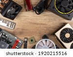 modern desktop computer hardware components on wood desk table background. Circle shaped out of pc parts like cpu fan cooler motherboard ram graphics card ssd and power supply wood technology concept.
