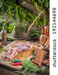 Hunting equipment and venison with herbs - stock photo