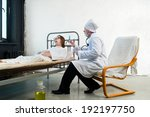 Small photo of Doctor and infirm patient in a hospital