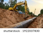 Small photo of Natural Gas Pipeline Construction. Gas and Crude oil transmission in pipe from gas storage and plant development to facility. Excavator and pipelayer during building of transit petrochemical pipes