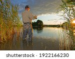 angler catching fish during summer sunset