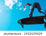 Small photo of Skater in action. Man making a trick on a longboard outdoors on sunny summer day. Blue sky background. Concept of extreme sport active lifestyle