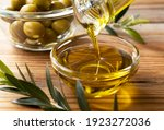 Small photo of The moment olive oil is poured into a glass bowl set against a wooden background