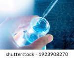 Small photo of hand of scientist holding flask with lab glassware and test tubes in chemical laboratory background, science laboratory research and development concept