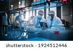 Small photo of Modern Medical Research Laboratory: Two Scientists Wearing Face Masks use Microscope, Analyse Sample in Petri Dish, Discuss Innovative Technology. Advanced Scientific Lab for Medicine, Biotechnology