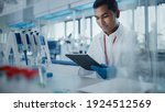 Small photo of Medical Research Laboratory: Portrait of a Handsome Male Scientist Using Digital Tablet Computer to Analyse Data. Advanced Scientific Lab for Medicine, Biotechnology, Microbiology Development