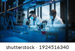 Small photo of Modern Medical Research Laboratory: Two Scientists Wearing Face Masks use Microscope, Analyse Sample in Petri Dish, Talk. Advanced Scientific Lab for Medicine, Biotechnology. Blue Color