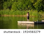 A Shirtless Man Fishing Off A...