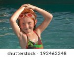 Small photo of little red haired girl wearing colorful togs and goggles in a hot pool in New Zealand