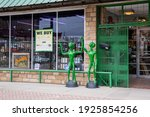 Small photo of Mineral Wells, Texas \ USA 02-25-2021 Exterior View of two green alien statues in front of Garrett's Store in Mineral Wells, Texas