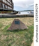 Long Wharf, Newport, Rhode Island, USA - A boulder with a historical marker that reads about the Steamships of the Fall River MNE 1847-1937.  Many docked boats, a stone wall, and steps to the water.