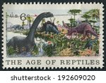 Small photo of United States of America-Circa 1970: A stamp titled The Age of Reptiles showing dinosaurs during the Jurassic.