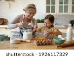 Small photo of Cooking with soul. Happy little girl in apron help senior grandma at kitchen mix dough for cookies pancakes. Smiling older granny teach small grandkid to bake homemade cake pastry share family recipe