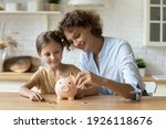 Small photo of Setting good example. Young parent mother teach child little daughter girl to manage finances save money spend earnings with economy plan family budget. Friendly mom and kid thrift coins in piggybank