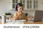 Small photo of Learning time. Interested little kid schoolgirl in headset sit at home desk watch education video lesson. Curious small school age girl think on teacher question select correct answer on laptop screen