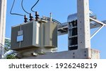 Small photo of Close up the transformer on a concrete pole. Three-phase transformers and rafts on rails for industrial plants on a blue sky background. Selective focus