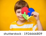 Small photo of Kid boy hands holding puzzle heart, child mental health concept, world autism awareness day, teen autism spectrum disorder awareness concept