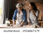 Small photo of Overjoyed adult Hispanic girl with senior mom make dough bake cookies pastries together on weekend. Happy millennial Latino woman with mature mother have fun cooking dessert at home kitchen.