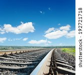 railroad to horizon under blue cloudy sky - stock photo