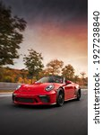 Small photo of Munich, Germany - January 10, 2021: A red Porsche 911 Speedster is driven on road