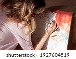 A young woman artist paints a...