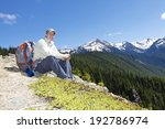 Happy man resting on rocks. Scenic view of mountains behind him - stock photo