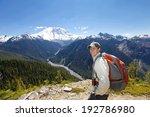 Happy traveler smiling. Scenic view of mountain Rainer behind him - stock photo