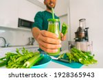 Small photo of Healthy man making fresh detox homemade celery juice in juicer machine at home and holding a glass bottle of celery juice. Healthy detox diet