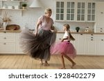 Small photo of Merry leisure time. Happy energetic grandmother teach ball dance active little child. Caring grandma junior girl grandkid engaged in dancing in funny large fluffy skirts barefoot on warm kitchen floor