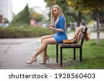 Beautiful blonde girl with phone in a blue dress with perfect legs in pantyhose and shoes with high heels sitting on the bench in the park.