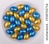 Small photo of Top view of a pile of blue and Yellow golden, wrapped in shiny tinfoil, chocolate Easter eggs in a white round bowl
