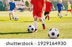Small photo of Sporty children on football summer camp. Kids practicing football on grass field. Football soccer children training class. Group of school children running and kicking soccer balls on training camp