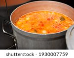 Small photo of A view inside a large stockpot full of simmering soup, in a restaurant kitchen setting.