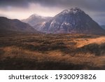 Small photo of Dramatic golden light on the dark, moody, mountain landscape of Buachaille Etive Mor with a distant Blackrock Cottage at Glencoe in the Scottish Highlands, Scotland.
