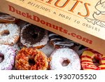 Small photo of Clarksburg, MD, USA 03-04-2021: A cardboard box of a dozen donuts bought from the chain store Duck Donuts. A popular selection of assorted donuts are made to order fresh