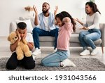 Small photo of Family Conflicts. Sad little black children covering ears with hands while their parents arguing in the background, upset boy and girl don't want to hear quarrel, stressed kid sitting on the floor