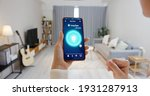 Small photo of Asian young woman is using smart home app and touch screen to turn on the light by mobile phone