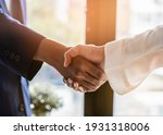 Small photo of contractor and Client shaking hands with team builder in renovation site.