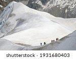 Trekkers Hiking A Snowy Ridge...