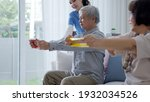 Small photo of Young older senior asia citizen couple sit on sofa couch with in-home nursing care, assisted living, scrubs nurse use resistance band exercise for senior patient in physiotherapy treatment at home.