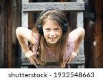 Small photo of Portrait of funny girlie enjoys music with headphones in the village outdoors.