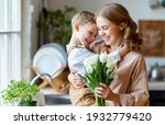 Small photo of Optimistic family: mother with bouquet of tulips laughing and touching forehead with happy son during holiday celebration mothers day at home