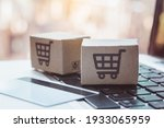 Small photo of Shopping online. Credit card and cardboard box with a shopping cart logo on laptop keyboard. Shopping service on The online web. offers home delivery