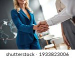 Small photo of Close up of female manager and client handshaking after making a deal at the travel agency office. Tourism, travelling, business concept