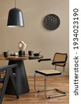 Small photo of Interior design of modern dining room space with stylish chairs, wooden table, black pedant lamp, decoration, ceramic vessel, teapot with cups. Fancy home decor. Template.