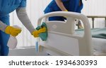 Small photo of Team of professional janitors using equipment disinfecting hospital ward. Nurses in uniform cleaning furniture in empty clinic room. Healthcare and hygiene concept